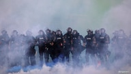 FILE PHOTO: Police officers are seen amid tear gas as protesters continue to rally against the death in Minneapolis police…