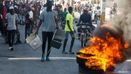 Demonstrators gather behind a burning barricade during protests against Haiti's President Jovenel Moise, in Port-au-Prince,…