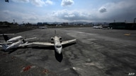 Three ash-covered aircraft remain on the tamrac at the La Aurora international airport, after authorities suspended its…