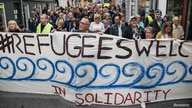 """People carry a banner reading """"#Refugees Welcome in solidarity"""" during a demonstration march in Aarhus, Denmark, September 12,…"""