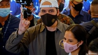 FILE PHOTO: El Salvador's President Nayib Bukele, accompanied by his wife Gabriela de Bukele, shows his finger after casting…