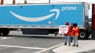 People hold a banner at the Amazon facility as members of a congressional delegation arrive to show their support for workers…