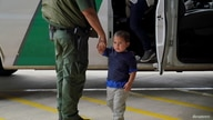 A Border Patrol agent holds an asylum-seeking child as his mother gets off the vehicle at the bus station after being processed…