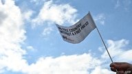 """A protester holds a flag reading """"no free country without a free press"""" to support """"reporters without borders"""" in Berlin on…"""