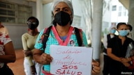 "A health worker holds a sign reading ""Starvation wages, SOS Health"" during a protest against the lack of vaccines against the…"