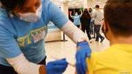 Nursing student Erika Lohr vaccinates a person as others are welcomed to a monitoring area following their shots as California…