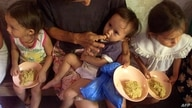 Olga Yanira is fed by her mother thanks to a  program created to fight hunger in Orcuina, Honduras 05 October 2002. Olga…