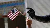 A girl holds a U.S. flag next to a sculpture after a naturalization ceremony at The Metropolitan Museum of Art in New York July…