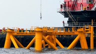 Workers look out from a construction barge next to the first jacket support structure installed to support a turbine for a wind…