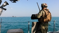 A United States Navy, security personnal stands watch oboard a Mark VI patrol boat while escorting the guided-missile submarine…