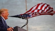 FILE PHOTO: FILE PHOTO: President Donald Trump speaks, with a flag behind him, during a campaign rally at Cecil Airport in…