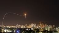 A streak of light is seen as Israel's Iron Dome anti-missile system intercepts rockets launched from the Gaza Strip towards…