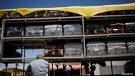 Vendors remove a tarp from the truck to deliver coffins to a funeral home as the coronavirus disease (COVID-19) outbreak…