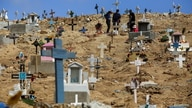 People stand among graves of victims of the coronavirus disease (COVID-19), and of others, at the municipal cemetery No. 12 in…