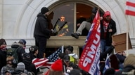 FILE PHOTO: A mob of supporters of then-U.S. President Donald Trump climb through a window they broke as they storm the U.S…