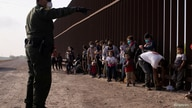 FILE PHOTO: A U.S. Border Patrol agent instructs asylum-seeking migrants as they line up along the border wall after crossing…