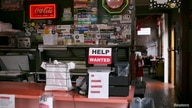 A hiring sign is seen at the register of Burger Boy restaurant, as many restaurant businesses face staffing shortages in…