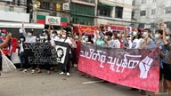 People carry banners as they protest in Yangon, Myanmar, in this still image from video obtained from social media dated June…