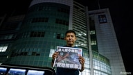 Apple Daily photographer Harry Long poses with the final edition of Apple Daily at its headquarters in Hong Kong, China June 24…