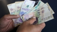 FILE PHOTO: A employee counts Colombian pesos at a store in Bogota, Colombia December 28, 2018. REUTERS/Luisa Gonzalez/File…