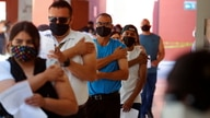 People hold their arms after receiving the Johnson & Johnson vaccine against the coronavirus disease (COVID-19), as part of a…