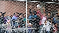FILE--In this March 27, 2019, file photo, Central American migrants wait for food in a pen erected by U.S. Customs and Border…