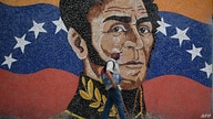 A man wearing a face mask walks past a mural depicting South American independence hero Simon Bolivar in Caracas on April 17,…