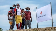 FILE PHOTO: Venezuelan refugees walk to a school where a temporary shelter has been set up, to receive medical assistance and…