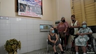 People wait after being vaccinated against the coronavirus under a poster displaying images of late Cuban President Fidel…