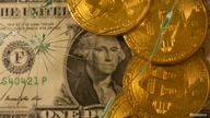 Representations of virtual currency bitcoin on top of a U.S. dollar banknote are pictured through broken glass in this…