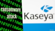 """A smartphone with the words """"Ransomware attack"""" and binary code is seen in front of the Kaseya logo in this illustration taken,…"""