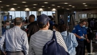 FILE PHOTO: Travellers line up to enter a Transportation Safety Administration (TSA) checkpoint, as domestic travel picks up as…