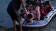 Asylum-seeking migrant families from Guatemala and Honduras arrive to the U.S. side of the bank on an inflatable raft after…