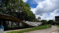 Venezuelan university students record a video with their cell phone next to a collapsed roof of the Central University of…