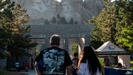 TOPSHOT - Visitors walk to see the Mount Rushmore National Monument  in Keystone, South Dakota on July 2, 2020. - US President…