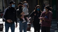 People wearing face masks walk along Plaza de Armas square in Santiago, on July 15, 2020, amid the new coronavirus pandemic. -…