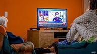 A family watches the live news showing Brazilian President Jair Bolsonaro announcing his positive result of the COVID-19 test…