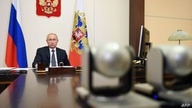 Russian President Vladimir Putin chairs a meeting with members of the government via a teleconference call at the Novo-Ogaryovo…