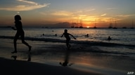 (FILES) In this file photo tourists play on a beach in Bridgetown, Barbados, as the sun sets on March 24, 2017. - Barbados has…