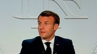 This picture shows a screen displaying French President Emmanuel Macron as he addresses the nation during a televised interview…