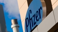 (FILES) In this file photo taken on March 18, 2017, a sign for Pfizer pharmaceutical company is seen on a building in Cambridge…