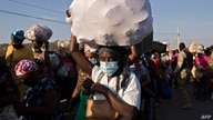 Haitian nationals carry products to sell at a market as they cross the bridge over the bordering Massacre River from…