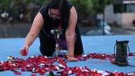 "A woman leaves flower petals at a makeshift memorial during a demonstration called ""Justice for Victoria"" for the death of…"