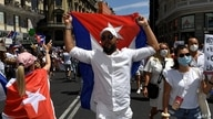 Protesters waving Cuban flags march along the Gran Via avenue in Madrid on July 25, 2021 in support of anti-government protests…