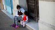 A woman and child sit on a door stoop in Buenos Aires, Argentina, Saturday, May 16, 2020. Children in the Argentine capital are…