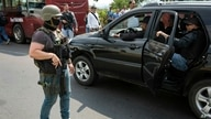 Members of FAES, special police commando unit, stands guard as a vehicle arrives to a concert at Tienditas International Bridge…