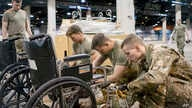 In this Monday, March 30, 2020, photo provided by the Illinois Air National Guard are members of the Guard assembling medical…
