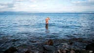A migrant who arrived recently from Turkey washes his hair in the sea at the village of Skala Sikaminias, on the Greek island…