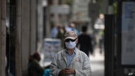 A man wearing a face mask to combat the spread of coronavirus waits to enter a shop in Madrid, Spain, Thursday, May 7, 2020…