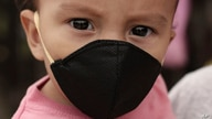 One-year-old Gael Gomez wears a mask against the spread of the new coronavirus, as his mother holds him and begs for food from…